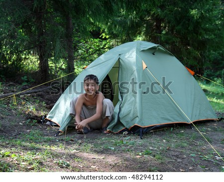 happy boy near camping tent in summer forest - stock photo
