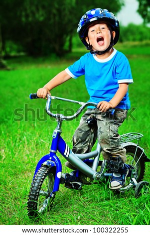 Happy boy on a bicycle in a summer park. - stock photo