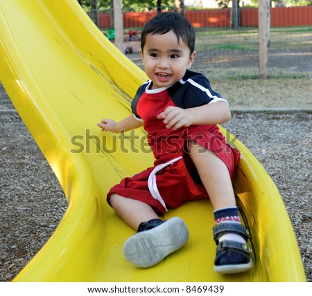 Happy Boy on a slide - stock photo