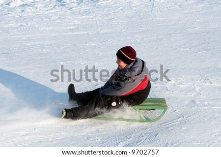 happy boy on sledge in bright winter day - stock photo