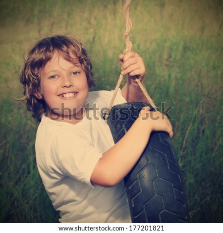 happy boy on swing outdoors - stock photo
