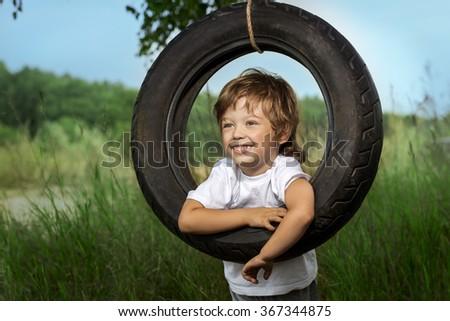 happy boy on swing outdoors - stock photo