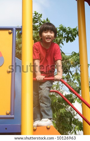 Happy boy playing at the playground in the park - stock photo