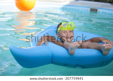 Happy boy playing in swimming pool  - stock photo