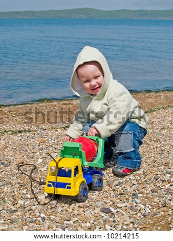 happy boy playing in the spring park on sea beach with toy - stock photo