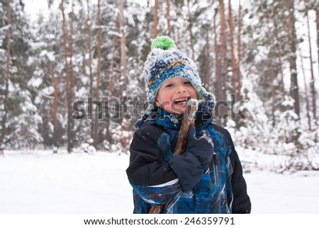 Happy boy playing in the winter with snow - stock photo