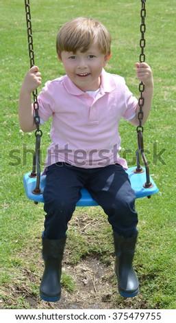 Happy boy playing on playground. - stock photo