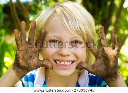 Happy boy playing outside with dirty hands - stock photo