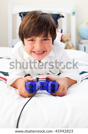 Happy boy playing video games in his bedroom - stock photo