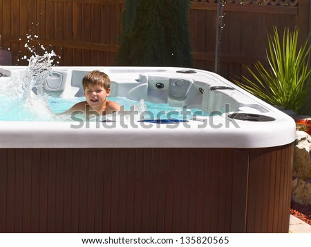 Happy boy playing with bubbles in hot tube on the back yard - stock photo