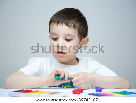 Happy boy playing with color play dough - stock photo