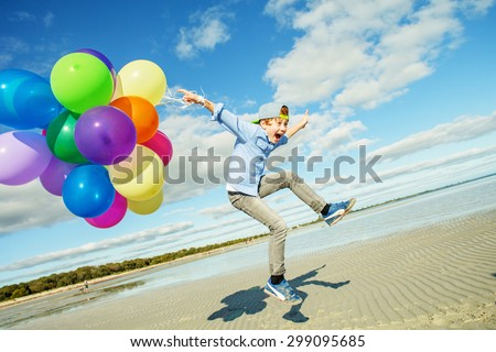 Happy boy plays with colored balloons on the beach having great holidays time on summer. Lifestyle, vacation, happiness, joy concept - stock photo
