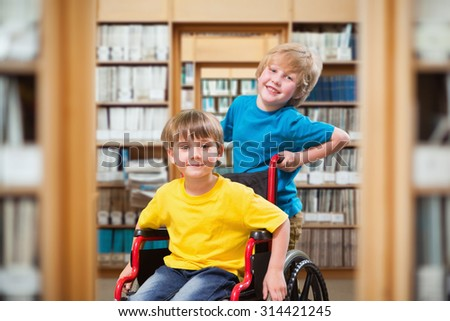 Happy boy pushing friend on wheelchair against library - stock photo