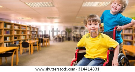 Happy boy pushing friend on wheelchair against view of library - stock photo