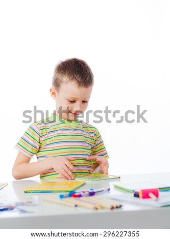 Happy boy read  book sitting by table - stock photo