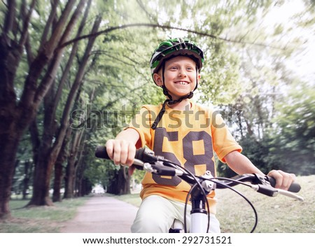 Happy boy ride a bicycle in city park - stock photo