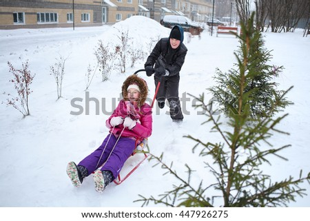 Happy boy rolling a girl on a sled near the apartment complex - stock photo
