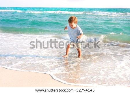 happy boy running in the sea