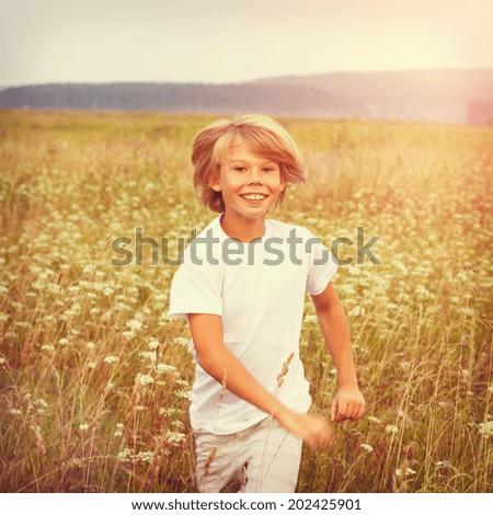 Happy boy running on summer field. - stock photo