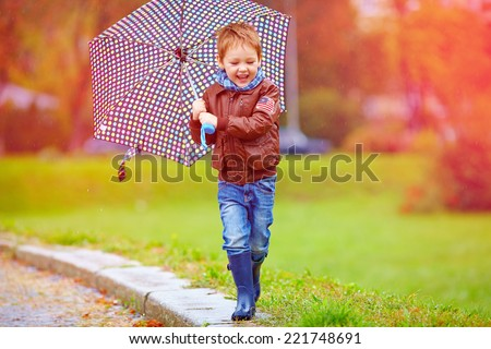 happy boy running under an autumn rain - stock photo