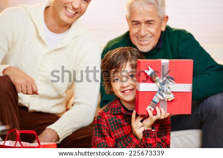Happy boy showing red gift at christmas with dad and granddad watching - stock photo