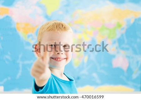 Happy boy showing thumbs up gesture in a classroom of geography