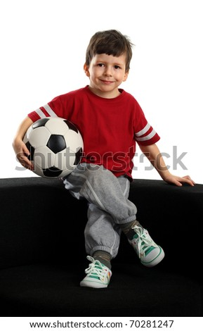 Happy boy sits with the soccer ball - stock photo