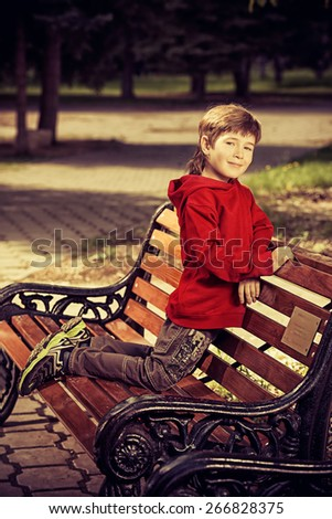 Happy boy sitting on the bench in the park. Summer day.  - stock photo
