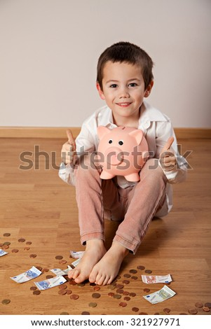 Happy boy sitting on the floor, collecting money in his piggy bank and showing ok - stock photo