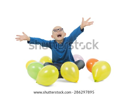 Happy boy sitting on the floor surrounded by balloons against a white background - stock photo