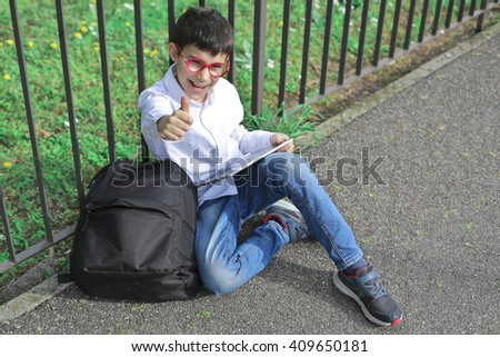 Happy boy sitting on the ground - stock photo