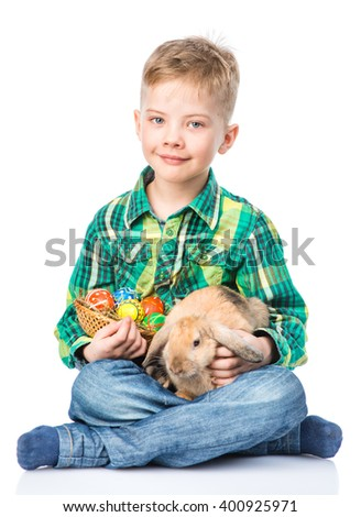 Happy boy sitting with easter eggs and rabbit. Isolated on white background