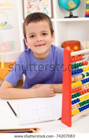 Happy boy solving math exercises in his room - stock photo