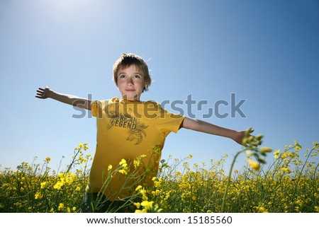Happy boy standing in canola field with open arms - stock photo