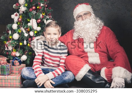 Happy boy surprised to see Santa Claus! Surprise for child! Xmas and New Year holiday. Your dad dressed in a Santa Claus costume! Christmas inspiration