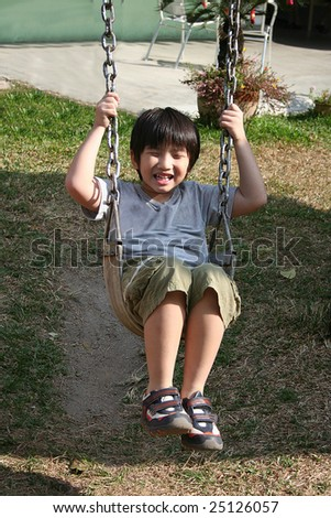 Happy boy swinging at the playground in the park on sunny day - stock photo