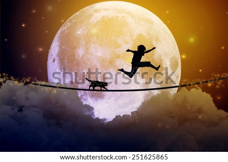 Happy boy teenager and cat jumping on a tight rope above clouds with moonlight moon background. Happiness friendship care free concept. Elements of this image furnished by NASA - stock photo