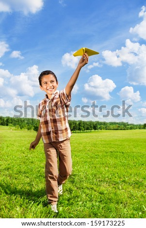Happy boy throwing paper plane running in the park on sunny day - stock photo