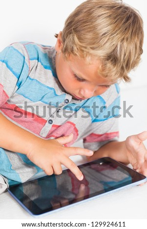 Happy boy touching a tablet lying on the floor