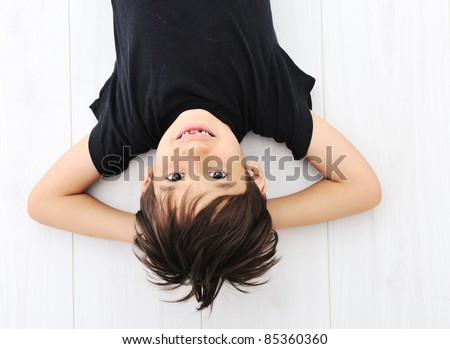 Happy boy upside down laying on white floor and smiling - stock photo