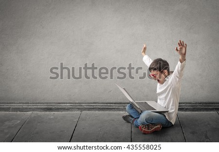 Happy boy using a laptop - stock photo
