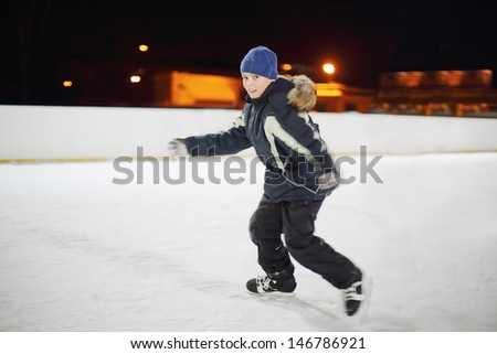 Happy boy wearing in black suit skates at dark winter night. - stock photo