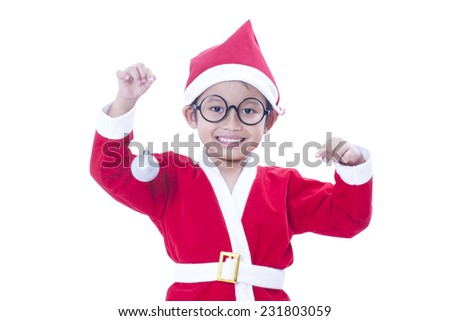 Happy boy wearing santa claus uniform and holding white christmas ball  - stock photo