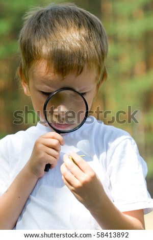 Happy boy with a magnifying glass  outdoors on a summer day - stock photo