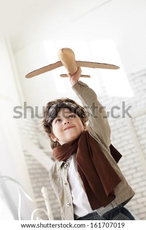 happy boy with airplane in hand - stock photo