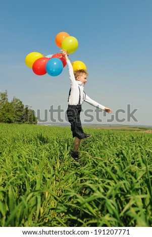Happy boy with balloons outdoors - stock photo
