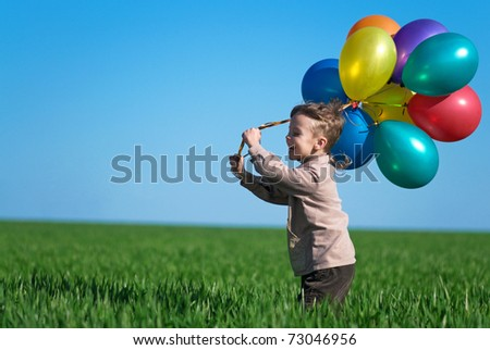 Happy boy with balloons running on the spring field - stock photo