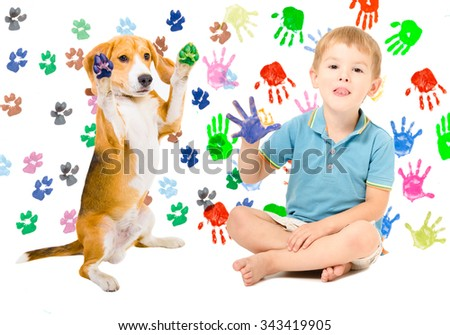 Happy boy with Beagle sitting  on the background of handprints - stock photo