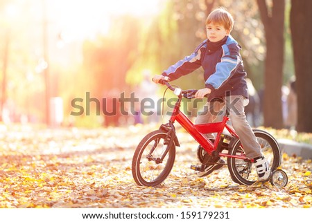 Happy boy with bicycle in the autumn park - stock photo