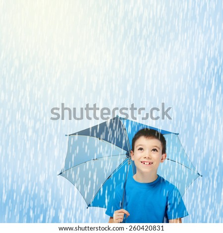 Happy boy with blue umbrella in the rain looking up - stock photo